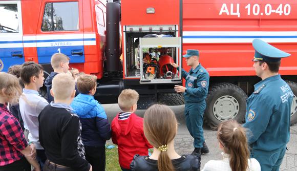 ■ Дмитрий Шавров демонстрирует детям пожарное оборудование