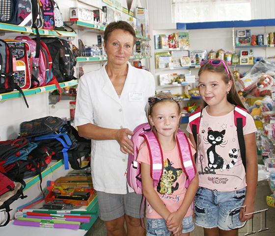 ■ Продавец отдела «Канцтовары и игрушки» Людмила Серая примеряет рюкзаки сестрам Демидович