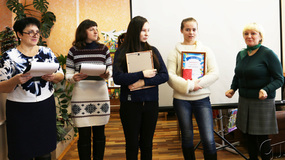 ■ Валентина Каминская (справа) и библиотекари Валентина Хартанович и Светлана Пукач поздравляют с победой Александру Попову и Анну Щеглову