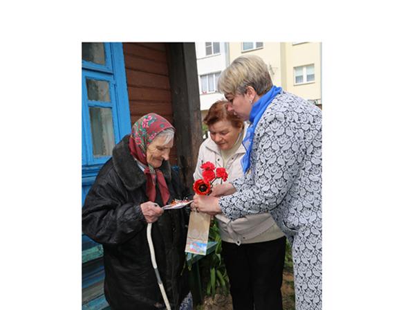 ■ Светлана Малиновская (справа) и Мария Дубовик вручают цветы и сувениры Наталии Васильевне Артамоновой