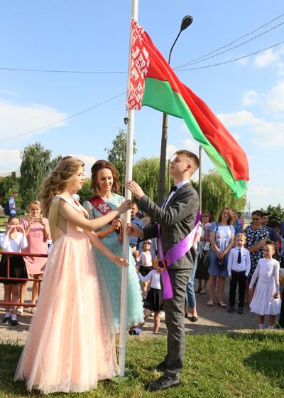 ■ Государственный флаг поднимают Даниэла Траянович, Вера Василевская, Евгений Новосад